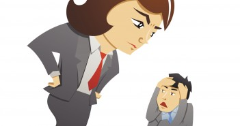 large female manager looking down on small male worker