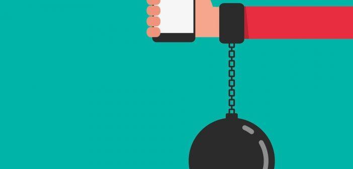 technology addiction handcuff on arm holding smartphone
